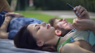Attractive young woman using smartphone. Couple friends rest in the park. Pair in love lie on the lawn grass and talking. Young family spend time at the open air in summer season. Girl typing message