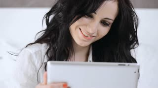 Attractive young woman using tablet computer touchscreen in her bedroom.