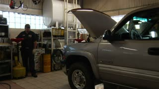Auto Mechanic Raising Car On Lift Platform