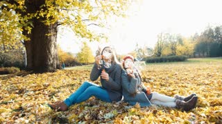 Autumn bubbles. Portrait mother and daughter blowing bubbles and sitting in the autumn leaves in the park and smiling at camera