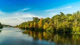 Autumn forest in yellow and red leaves on the edge of the river in the sky many clouds, no birds, smooth ponarama 4k timelapse