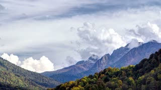 Autumn in High Mountains. Sochi, Russia. Krasnaya Polyana timelapse. View to trees and cloudy sky