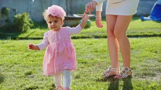 Baby girl is doing her first steps with mothers help. Slow Motion 240 fps. Cute little toddler is learning to walk and her young mom helping her in the sunny garden outdoors. Happy childhood concept.