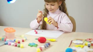 Baby girl paint the wooden figure toy. Fine Art How lesson