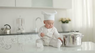 Baby in hat sitting on kitchen table. He holding a soup ladle