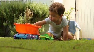 Baby toddler playing in outdoor grass with toys