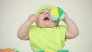 Baby with a cap playing with a ball