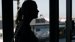 Back-lit silhouette of a young woman drinking coffee at the airport and looking through the window at the airplanes