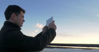 Back view of a adult man with tablet pc computer on cruise ship shoots the sea sunrise