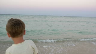 Back view of a little boy alone on the beach. He standing by the sea and looking as waves coming close to his feet