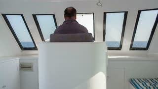 Back view of a man driving a yacht