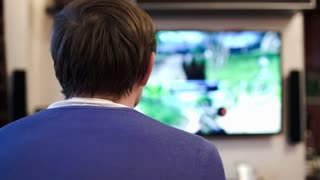 Back view of a man playing shooter video game shown on big screen