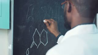 Back view of a student writing a chemical formula on the blackboard
