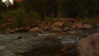 Backpacker Sits On Rock In Creek, Moutains Near