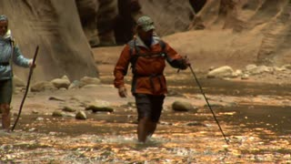 Backpacking Couple Walk Through Water In Canyon