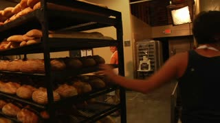 Baker Pushes Rack Of Fresh Loaves Of Bread