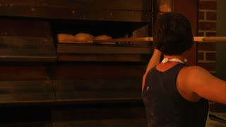 Baker Removes Loaves Of Bread From Oven