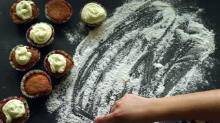 Baking concept. Finger writing word baking on flour at kitchen table. Inscription baking on white flour spills at table. Baked cupcakes on kitchen table