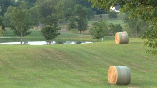 Bales of Hay In Front of Pond and House