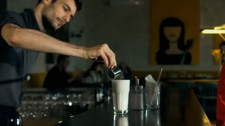 Barista is pouring milk in a latte cup. HD cinemagraph - motion photo seamless loop. Shot with Blackmagic URSA Mini