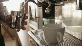 Barista makes latte cappuccino in coffee machine
