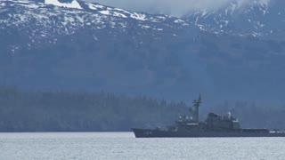 Battleship Streaking Past Mountains