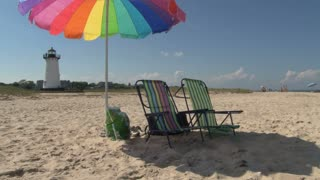 Beach Chairs and Umbrella in Front of Lighthouse