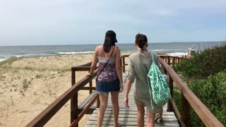 Beach. steadycam shot of two women walking by walkway path to the beach shore