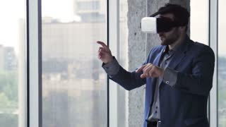 Bearded businessman in oculus rift gesturing and talking near window