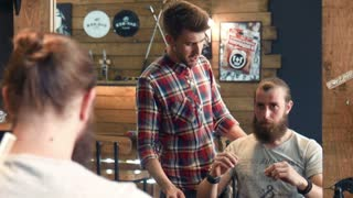 Bearded man showing to barber how to groom his beard in mirror