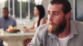 Bearded man with tall glass and pony tail relaxes in outdoor cafe with trendy furnishings