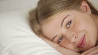 Beautiful blonde girl lying in bed looking at camera and smiling. Panning camera