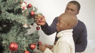 Beautiful boy decorating the christmas tree with his father
