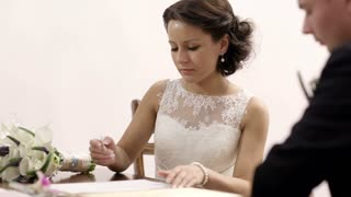 Beautiful bride signing marriage license in register office. Groom sitting near by. Photoflashes blinking.