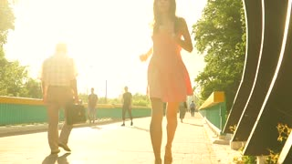 Beautiful brunette girl in pink dress runs though arched passage. Slow motion steadicam clip