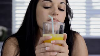 beautiful brunette woman drinking orange juice in modern kitchen with tablet computer