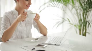 Beautiful businesswoman sitting at table with cup of coffee