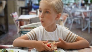 Beautiful girl eating pizza in cafe and looking at camera. Child sitting and smiling