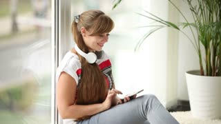 Beautiful girl in headset sitting by window using cellphone looking at camera and smiling
