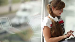 Beautiful girl in headset sitting by window using laptop looking at camera and smiling. Panning camera