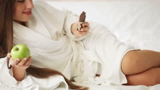 Beautiful girl lying in bed holding ba of chocolate and green apple looking at camera and smiling. Panning camera