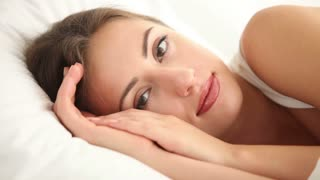 Beautiful girl lying in bed looking at camera closing her eyes and falling asleep