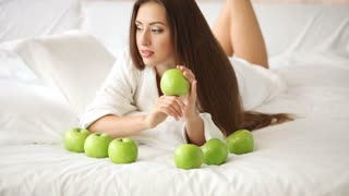 Beautiful girl lying on bed with apples holding one and smiling at camera. Panning camera