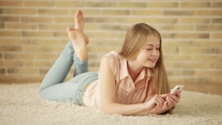 Beautiful girl lying on carpet using mobile phone looking at camera and smiling