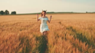 Beautiful girl running on sunlit wheat field. Slow motion 120 fps. Freedom concept. Happy woman having fun outdoors in a wheat field on sunset or sunrise. Slowmo. Harvest.