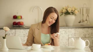 Beautiful girl sitting at kitchen table with laptop holding mobile phone and eating cake