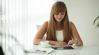 Beautiful girl sitting at table drinking coffee using touchpad looking at camera and smiling