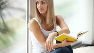 Beautiful girl sitting by window reading book looking at camera and smiling. Panning camera