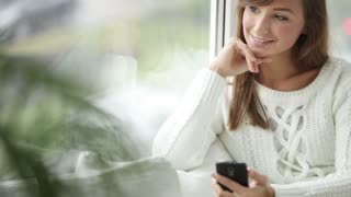 Beautiful girl sitting by window using mobile phone looking at camera and smiling. Panning camera