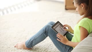 Beautiful girl sitting on floor using touchpad looking at camera and smiling. Panning camera